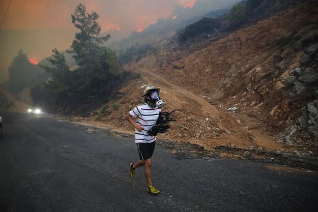 En man springer från lågorna i turkiska Milas i provinsen Mugla vid Medelhavskusten.