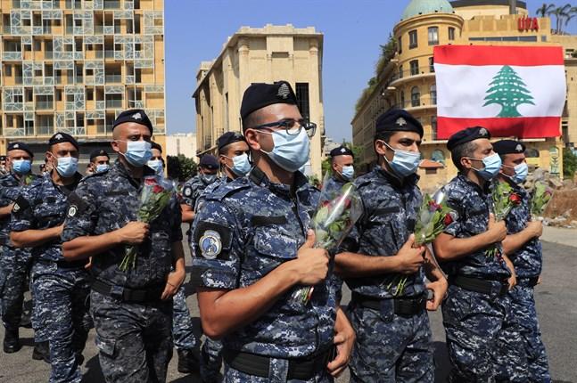 Polis bär på buketter under årsdagen av den massiva explosionen i Beiruts hamn den 4 augusti 2020.