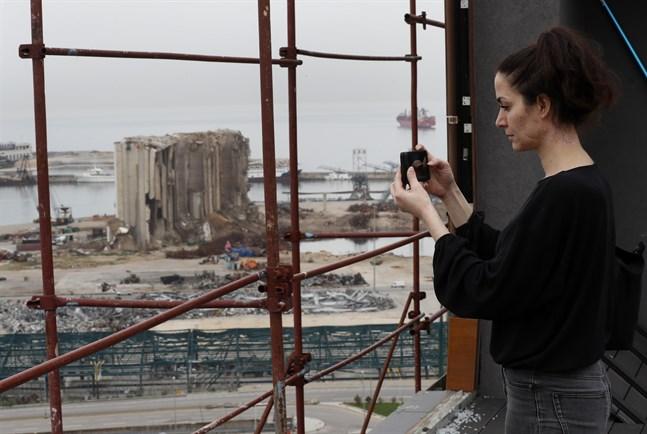 Joana Dagher, 33, som överlevde den våldsamma explosionen i Beirut förra året, tar en bild av hamnen ett halvår efter detonationen.