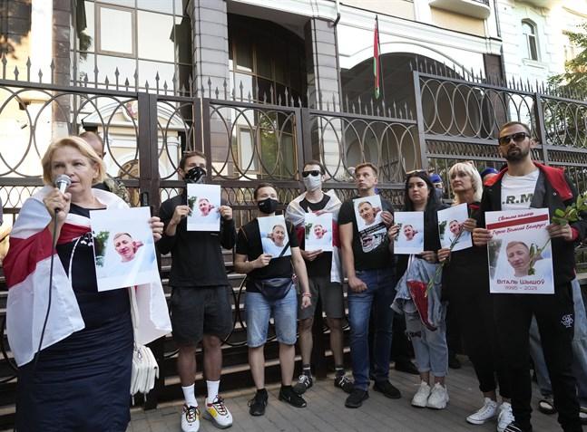 Belarusier håller upp porträtt på Vitalij Sjisjov utanför Belarus ambassad i Kiev.