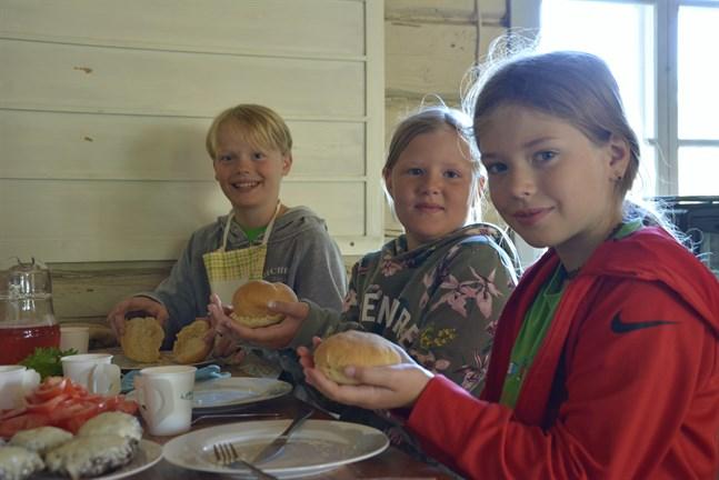 Lea Ingberg, Alma Backfolk och Anton Nordström visar upp sina hembakade hamburgerbröd som de gjorde under tisdagen i matskolan på Vargberget.