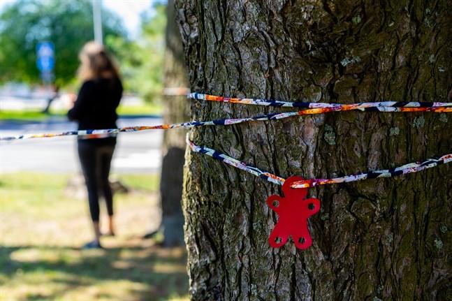 En figur i konstläder får skydd bakom ett träd.
