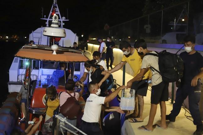 Människor evakueras i båtar efter att en markbrand nått kolkraftverket Kemerkoy i Milas i sydvästra Turkiet.