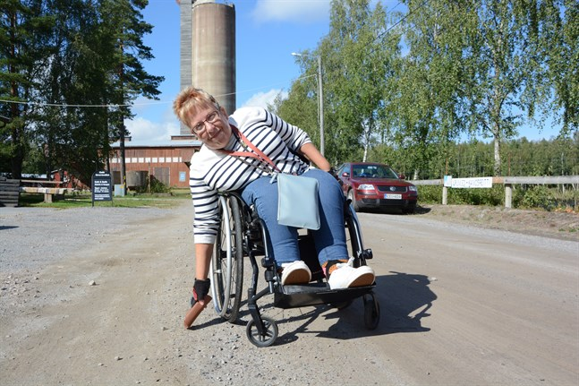 Stina Österbro demonstrerar ett moment i sommarens rullstolsbana vid Korsnäs gruvcenter i sommar: att lyfta en sak från marken.