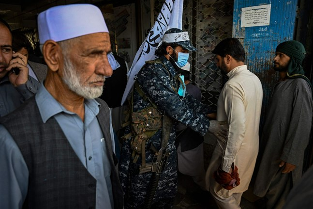 En talibansoldat kroppsvisiterar en man på en marknad i Kabul.