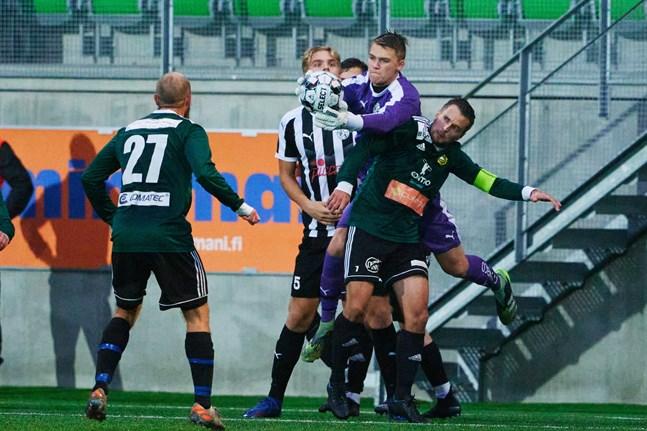 Antti Latva-Kivistö plockar åt sig bollen framför näsan på Sundom IF:s lagkapten Ludwig Siegfrids. VPS-målvaktens match tog slut efter att han slagit ena axeln ur led.
