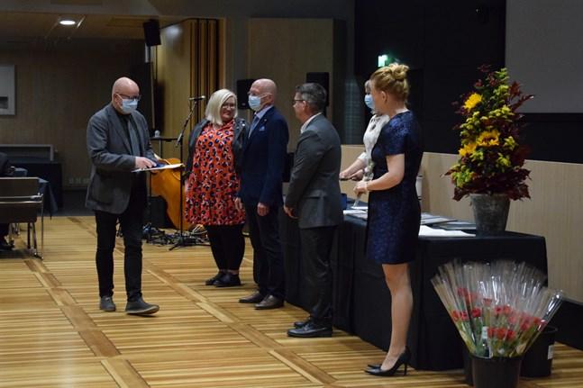 Tom Johanson får förtjänsttecken i silver och gratuleras av Tiina Isotalus, Stefan Anderson, Tapio Pajunpää och Sari Innanen. Bakom bordet Sonja Remell.