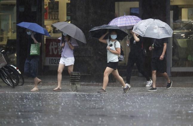 Folk med paraplyer i Taiwans huvudstad Taipei tar skydd undan skyfall efter tyfonen Chanthus framfört på ön under helgen.