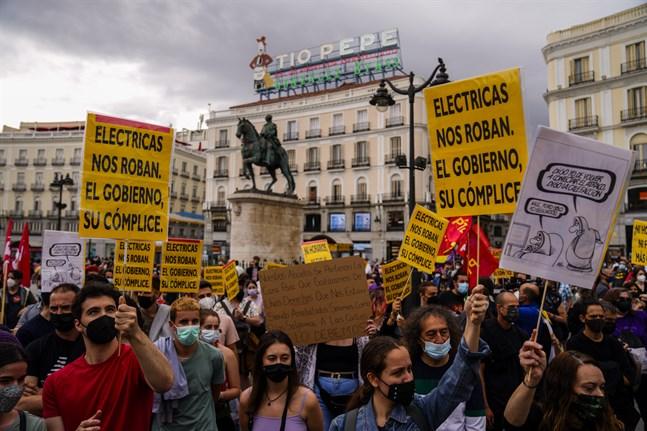 """Protester i Madrid i somras mot höga elpriser: """"Elbolagen rånar oss och regeringen är deras medbrottsling"""", står det bland annat på plakaten. Arkivbild."""