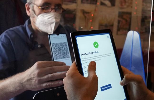 """En besökare visar upp sitt """"gröna pass"""" på väg in till en biograf i Milano. Bild från den 6 augusti."""