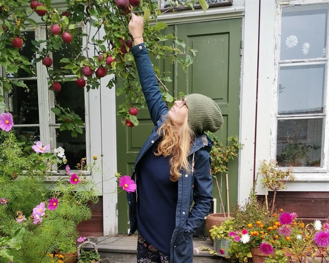 Maria Österåker kommer delta i #dagenshållbarhetsoutfit. På bilden är hon klädd i en jacka för fem euro, ribbstickad mörkblå tröja för en euro, blommiga tights för en euro och skor för två euro. Mössan har minst 15 år på nacken.