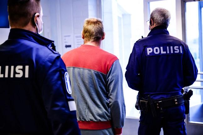 Den åtalade mannen förs in i rättssalen i Karleby tingsrätt av polis.