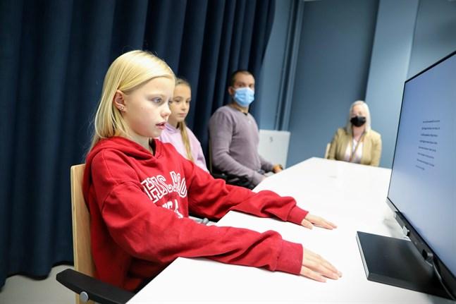 My Äijänens läser texten högt och får sedan frågor om den. Bakom henne syns Hilda Backlund, Thomas Södergård och Carolina Lassus. När VBL inte är på besök sitter eleven ensam i rummet med den som håller i trådarna för testet.