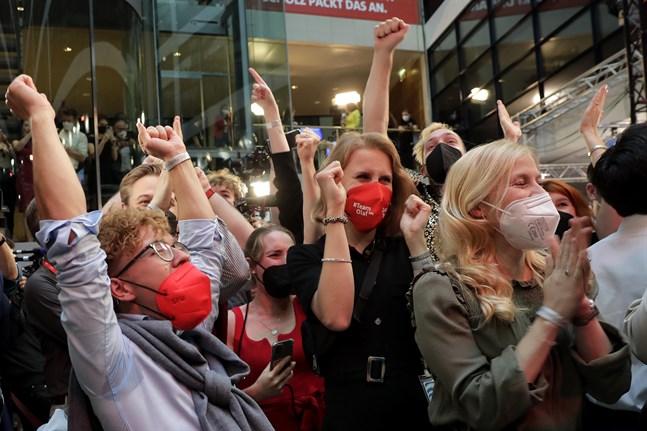 Socialdemokrater jublar när de första prognoserna kommer upp på tv-skärmarna i högkvarteret Willy-Brandt-Haus.