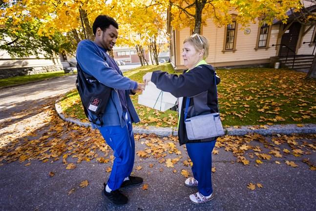 Sjukskötaren Mohamed Ibrahim tar emot en smörgås av kollegan Katja Lagström.
