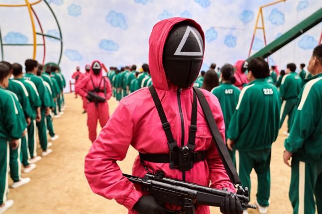 """""""Squid game"""" handlar om en mystisk tävling som styrs av beväpnade, maskförklädda män. Grönklädda deltagare tävlar med livet som insats. Pressbild."""