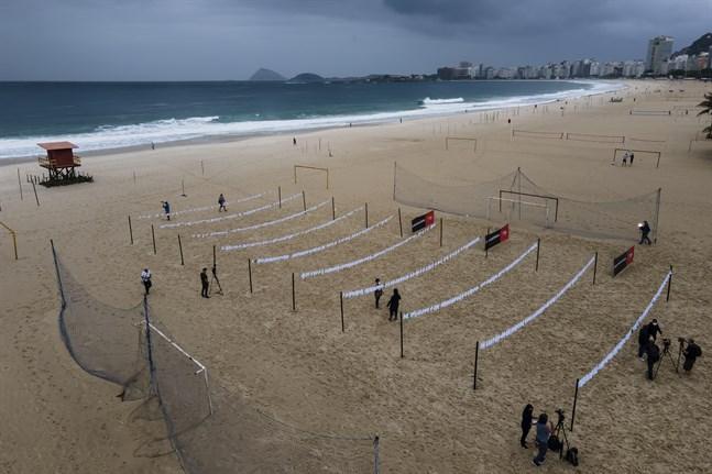 Vita näsdukar som symboliserar avlidna i covid-19 har hängts upp på stranden Copacabana i Rio de Janeiro.