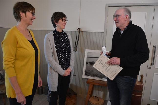 Yvonne Sjöström, som är styrelsemedlem i Norrnäs uf, och hembygdsförbundets verksamhetsledare Susanne Lagus tycker Anders Wester är väl värd hembygdsmedaljen i silver med blåvitt band och diplom.