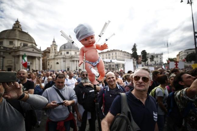 En docka med sprutor vid en protest i huvudstaden Rom mot vaccinpassen. Bilden är tagen i lördags.